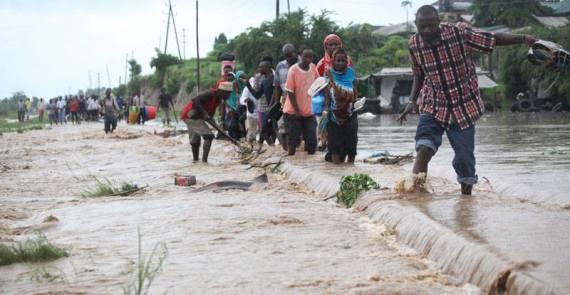 Wakazi wa Tabata Kisiwani wakipita katikati ya reli iliyofurika maji kutokana na mvua zilizonyesha Dar es Salaam
